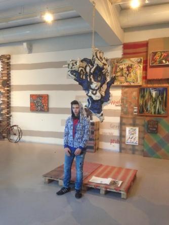 Adnan poseert met een hangend object dat hem aansprak vanwege de gekke kleur en vorm.