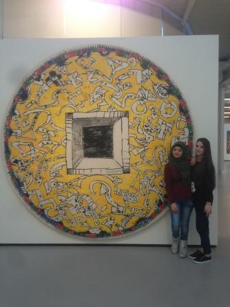 Seba en Nagham met een kunstwerk van Pierre Alechinsky. De ronde vorm en gele kleur vonden ze erg mooi.